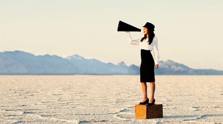 Femme qui crie dans un mégaphone dans le désert